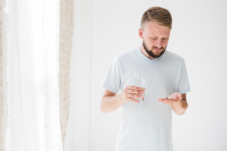 Homem segurando copo de água e comprimido