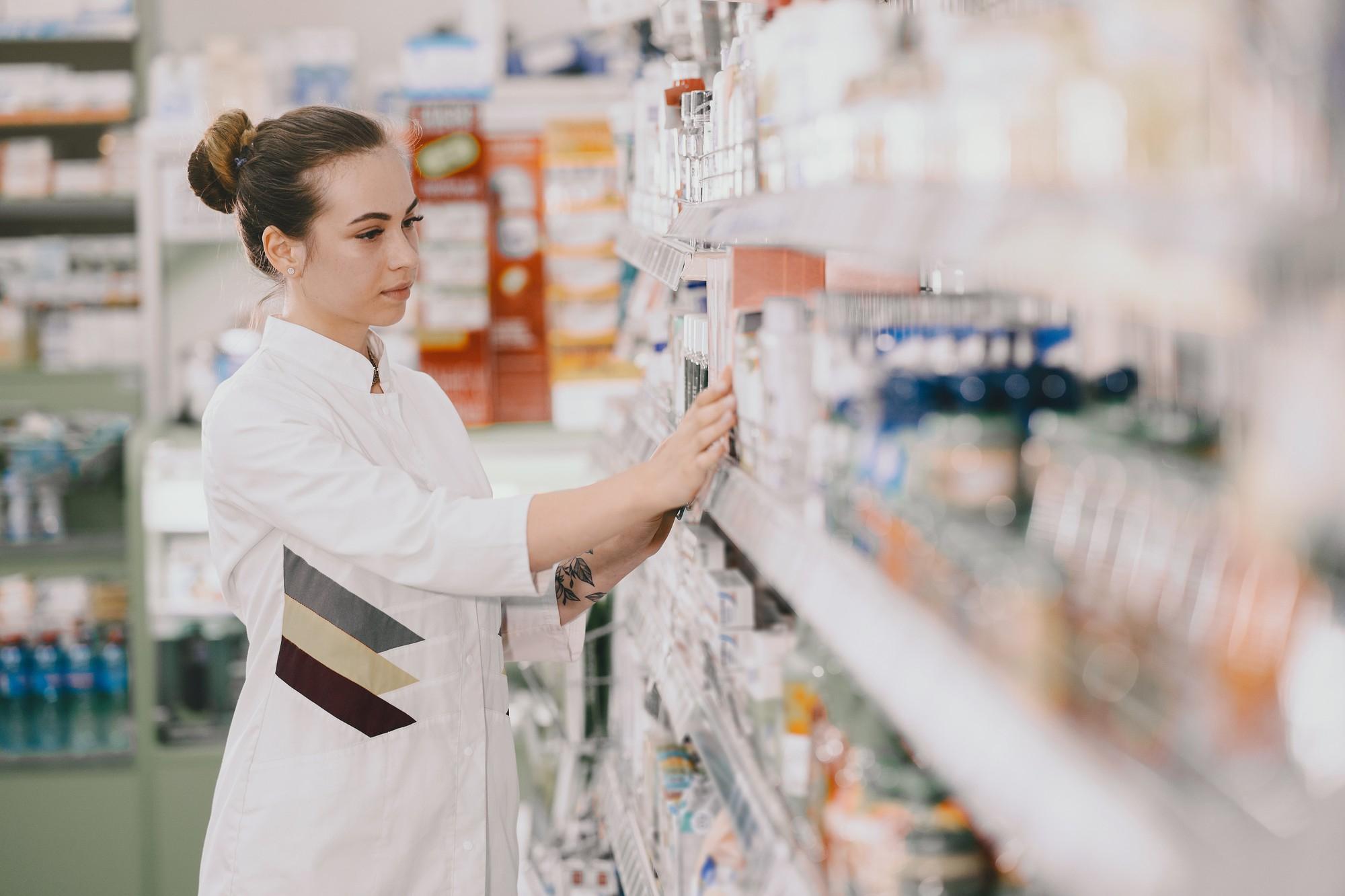 Farmacêutica escolhendo medicamento importado em prateleira
